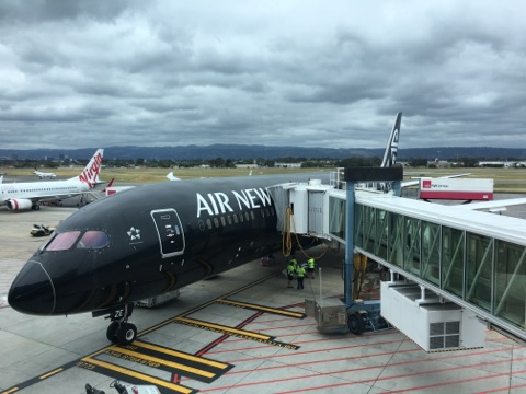 Air New Zealand Dreamliner 787-9 parked at the gate while storm clouds loom in the distance